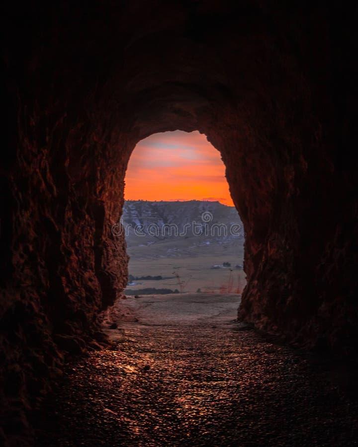 Utgångshål av en funnen gammal grotta i en öken med steniga kullar och solnedgången i bakgrunden royaltyfri bild