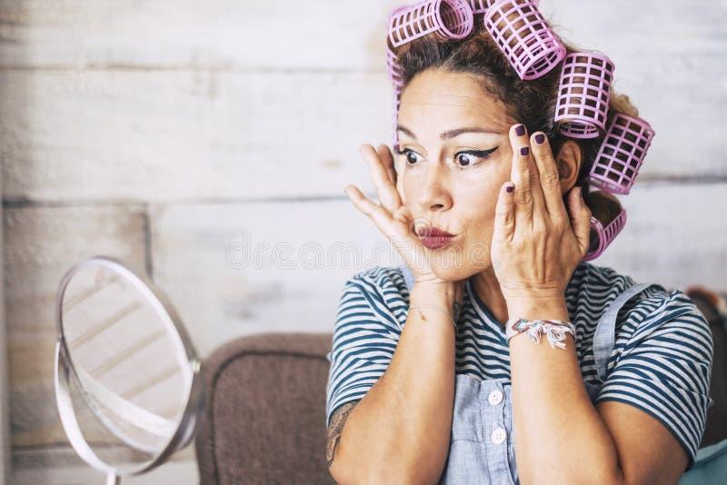 Utgör den caucasian vuxna kvinnan för det härliga och roliga uttryckt som får klar hemma framme av spegeln med, på framsidan - royaltyfri bild