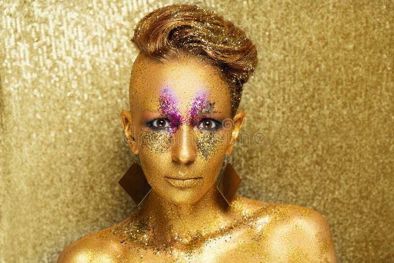Utgör den guld- framsidan för kvinnan arkivfoton