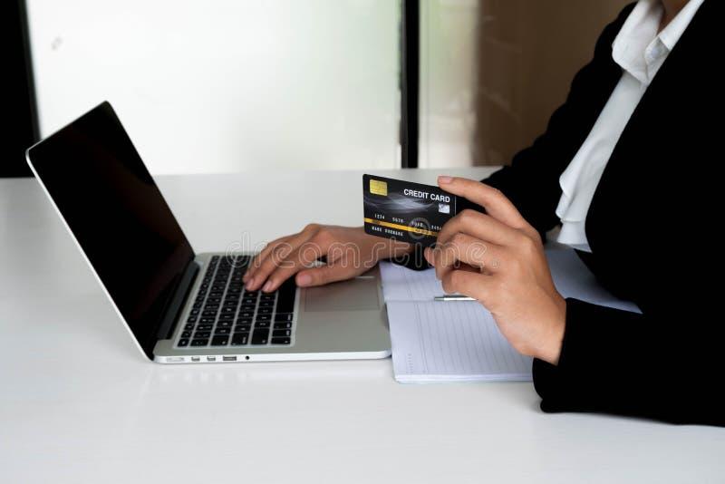 Utgifter för affärskvinnakonsument via kreditkorten för online-shopping på hennes bärbar dator arkivfoto