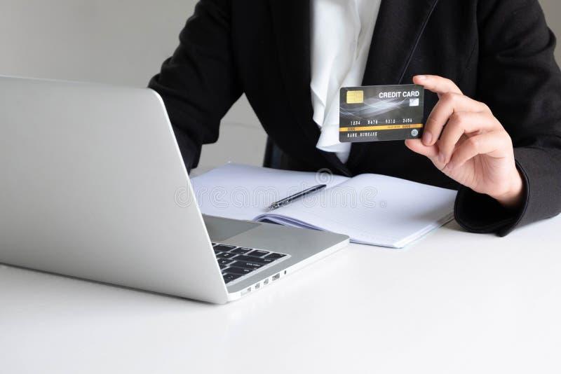 Utgifter för affärskvinnakonsument via kreditkorten för online-shopping på hennes bärbar dator arkivbild