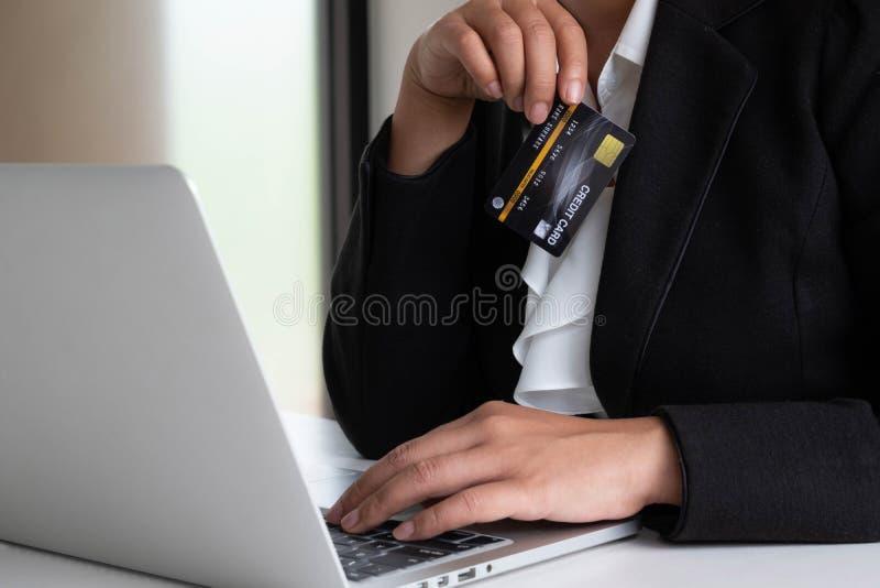 Utgifter för affärskvinnakonsument via kreditkorten för online-shopping på hennes bärbar dator royaltyfria foton