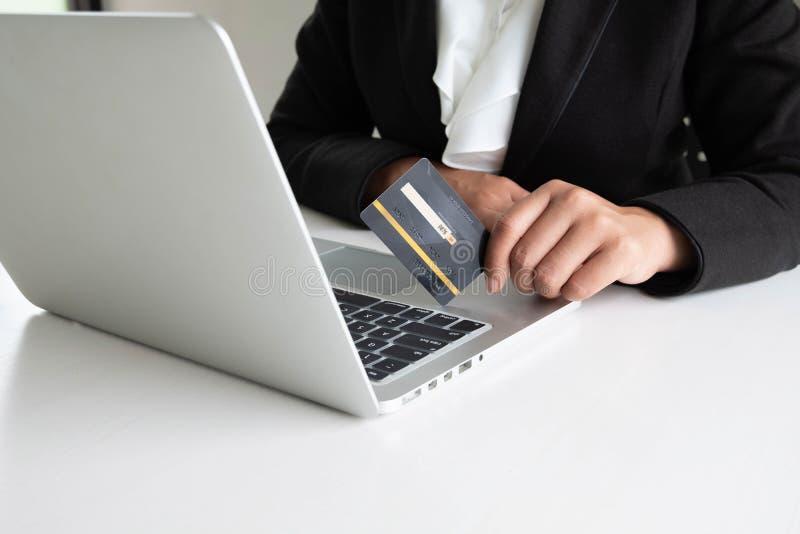 Utgifter för affärskvinnakonsument via kreditkorten för online-shopping på hennes bärbar dator arkivfoton