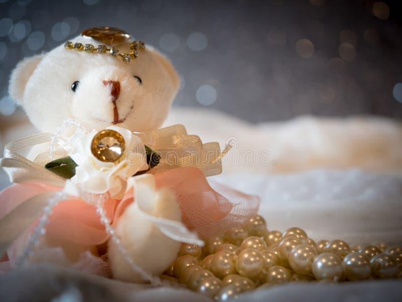 Uthärda den bärande bröllopsklänningen för dockabruden på lyxig bakgrund royaltyfri bild