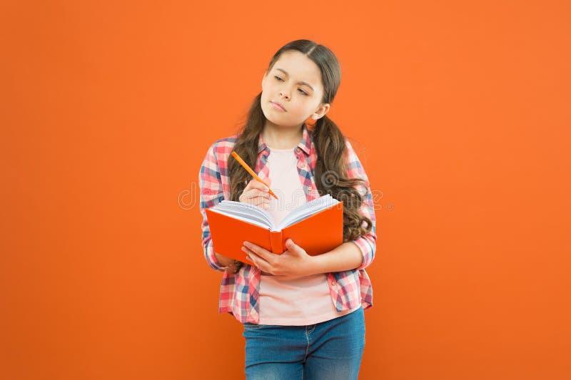 Uth?rdat f?r att l?sa F?rtjusande liten flicka som l?r att l?sa och skriva p? orange bakgrund Det gulliga sm?barnet kan l?sa en b arkivbilder