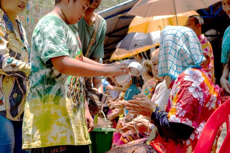 UTHAI THANI, THAILAND - 13. April Kinder bitten um Segen von den Erwachsenen am Tag des Songkran-Festivals, das ein großes ist stockfotografie