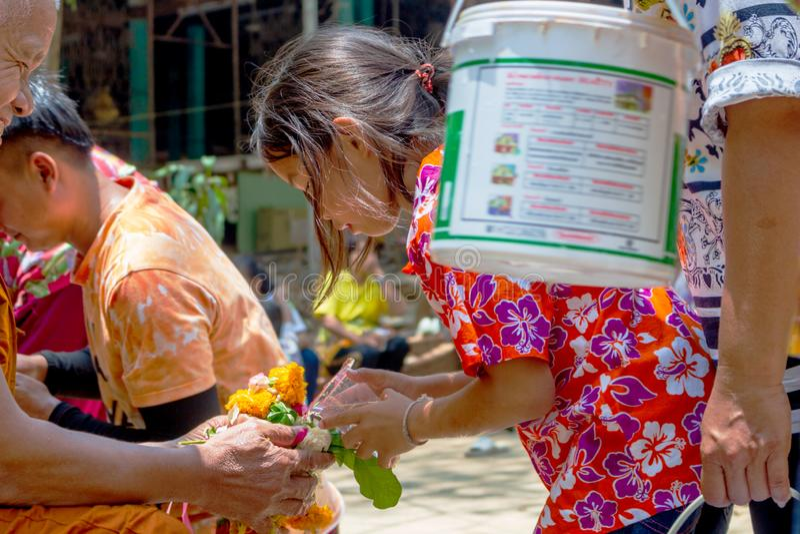 UTHAI THANI, THAILAND - 13. April Kinder bitten um Segen von den Erwachsenen am Tag des Songkran-Festivals, das ein großes ist lizenzfreies stockbild