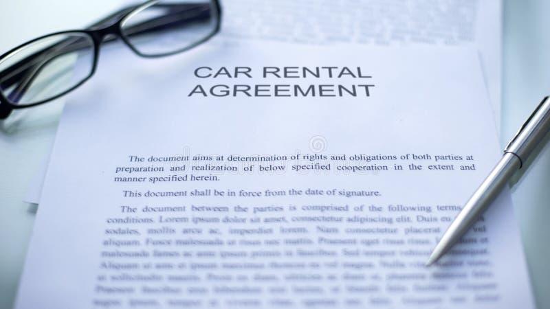 Uthyrnings- överenskommelse för bil som ligger på tabellen, penna och glasögon på officiellt dokument arkivbild