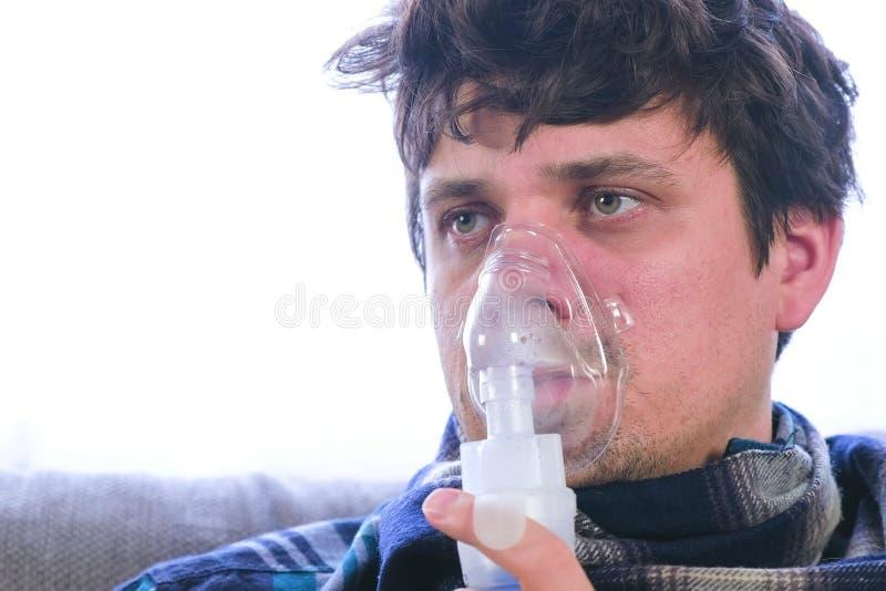 Utilice el nebulizador y el inhalador para el tratamiento Hombre enfermo que inhala a través de máscara del inhalador foto de archivo