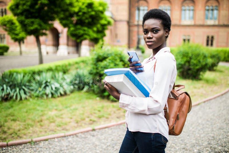 Utilice este app Estudiante joven feliz del afroamericano uni que usa el teléfono celular imágenes de archivo libres de regalías