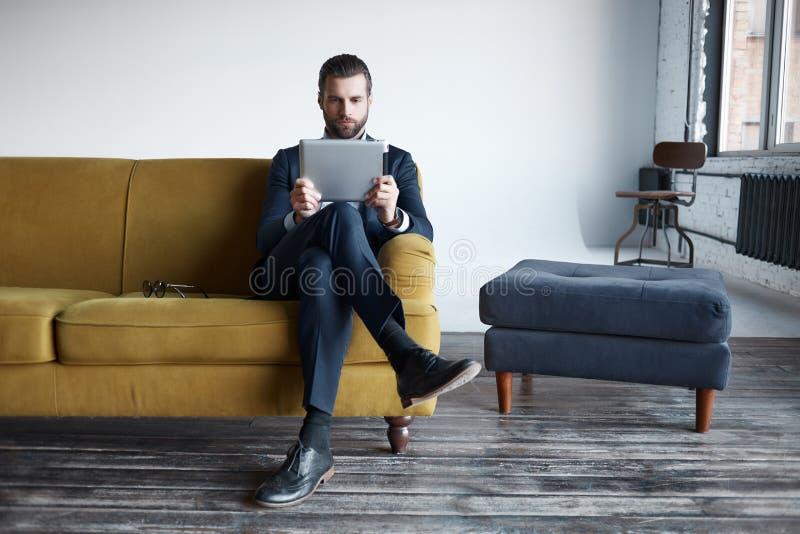 Utilisant des technologies modernes L'homme d'affaires réfléchi barbu regarde le comprimé numérique tout en se reposant sur le so images stock