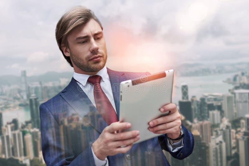 Utilisant des technologies modernes Portrait en gros plan d'homme d'affaires barbu attirant dans le costume utilisant le moment n photo stock