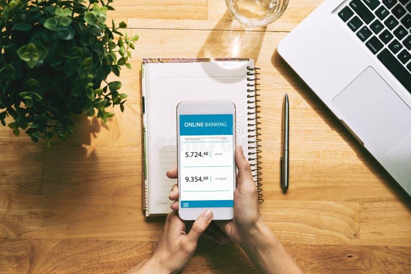 Utilisant l'application d'opérations bancaires en ligne photos stock