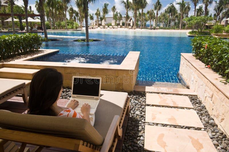 Utilisant l'ordinateur à la pièce de lagune d'hôtel images stock