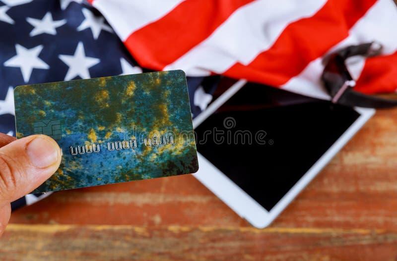 Utilisant la carte de crédit sur le drapeau des USA sur le comprimé numérique, faisant des emplettes en ligne image libre de droits
