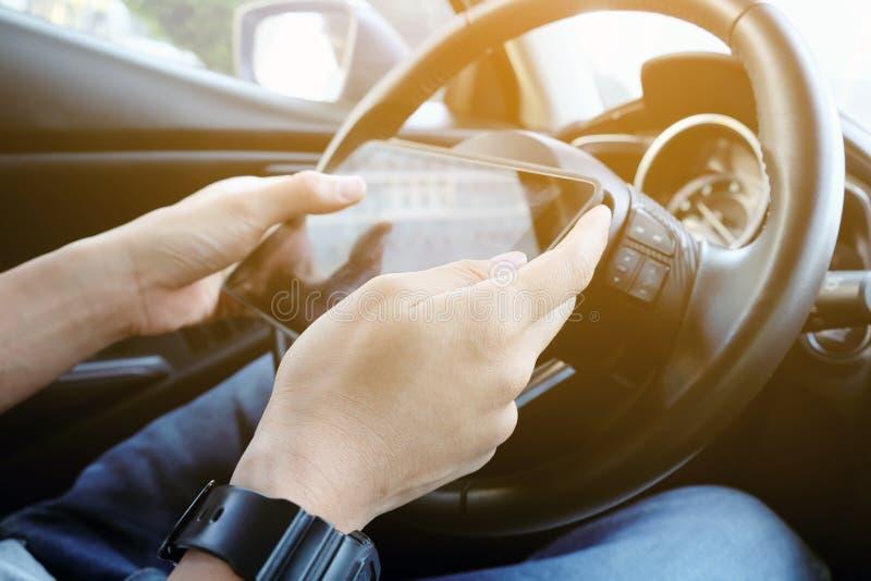 Utilisant le comprimé numérique tout en conduisant la voiture photos stock