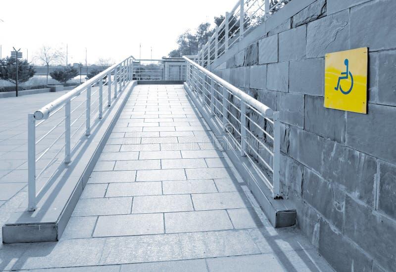Utilisant le rampe de fauteuil roulant images libres de droits