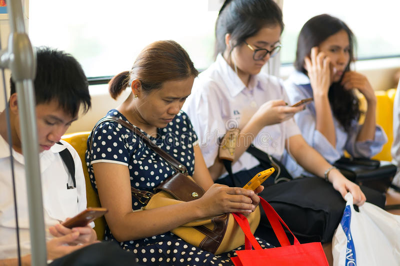 Utilisant le smartphone dans le transport en commun images libres de droits