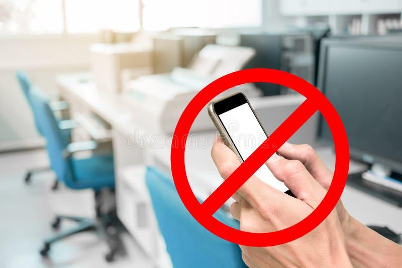Utilisant le smartphone n'est pas permettre dans le bureau fonctionnant photographie stock libre de droits