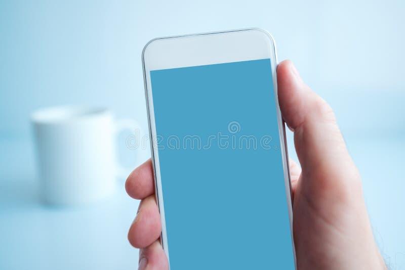 Utilisant le smartphone pendant la pause-café pendant le matin photo stock