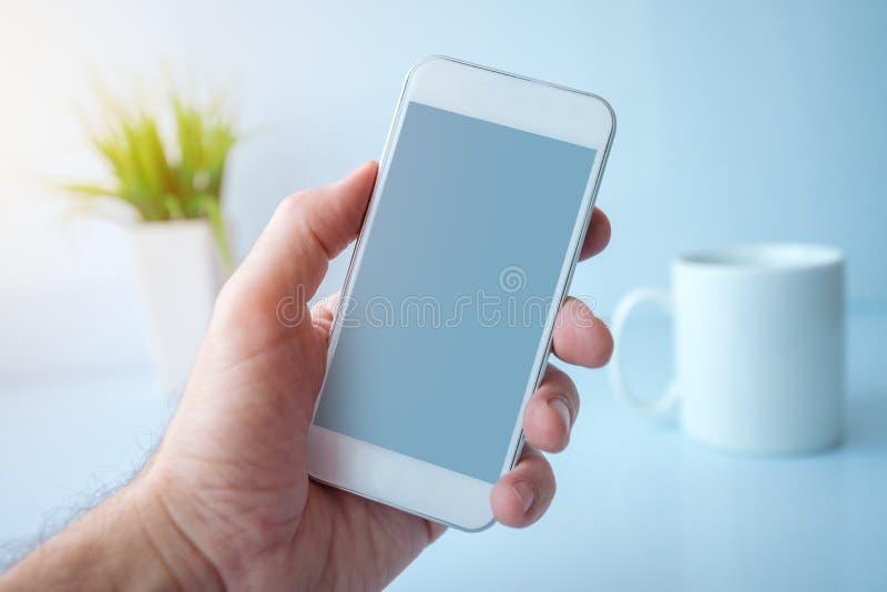 Utilisant le smartphone pendant la pause-café pendant le matin images stock