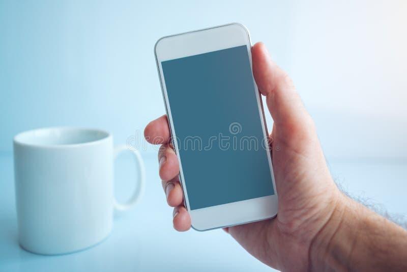 Utilisant le smartphone pendant la pause-café pendant le matin photographie stock