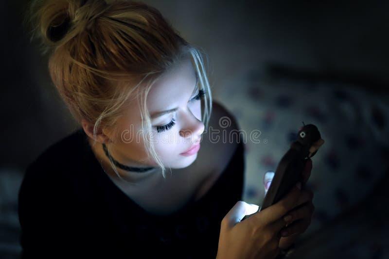 Utilisant le smartphone sur le lit photos libres de droits