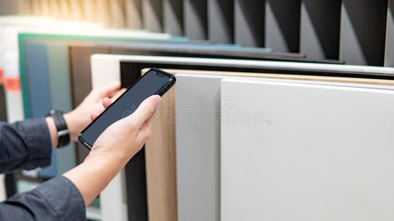 Utilisant le smartphone tout en choisissant des matériaux d'armoire photo stock