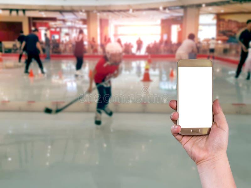 Utilisant le téléphone intelligent mobile avec le fond de tache floue de patinage de glace, Vintag image libre de droits