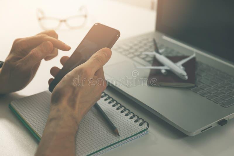Utilisant le téléphone intelligent pour la réservation en ligne de billet et d'hôtel de vol images libres de droits