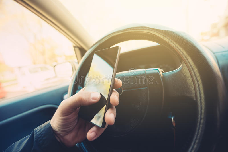 Utilisant le téléphone portable et la voiture d'entraînement image libre de droits