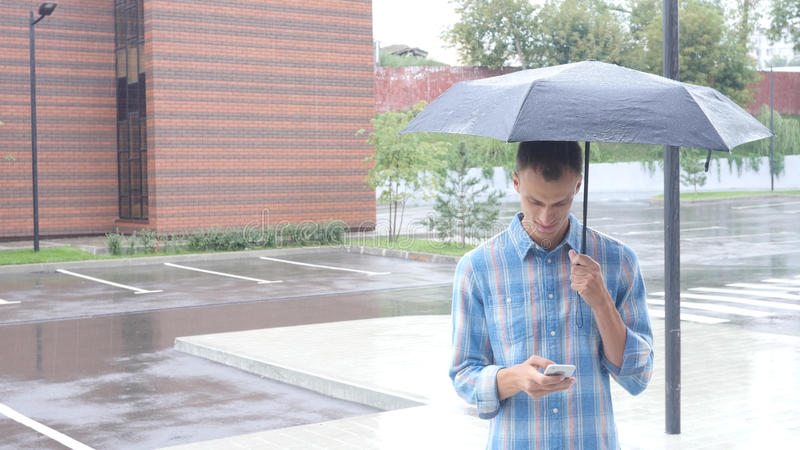 Utilisant Smartphone, se tenant sous le parapluie pendant la pluie image stock