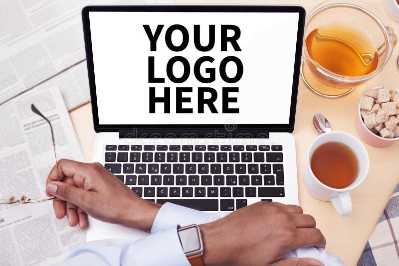 Utilisant un ordinateur tout en buvant du thé photographie stock libre de droits