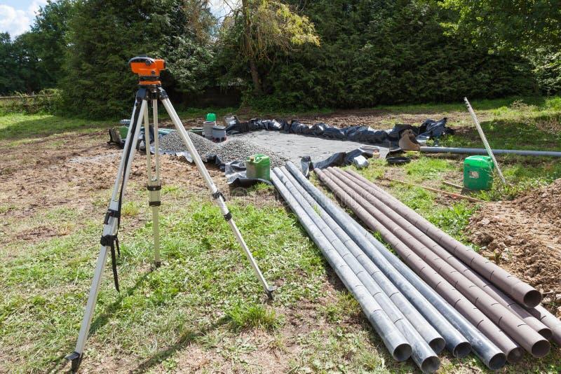Utilisant un théodolite pour installer une couche filtrante de gravier sur une fosse septique photo libre de droits