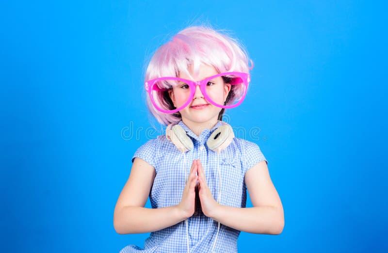Utilisateur adorable de casque avec les mains de prière Petit enfant portant le casque blanc réglable et la perruque rose de ch photo libre de droits