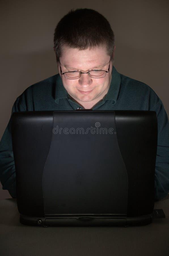 Utilisateur d'ordinateur dans la chambre obscurcie photographie stock