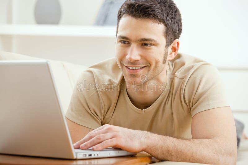 utilisation à la maison d'homme d'ordinateur portatif photos libres de droits