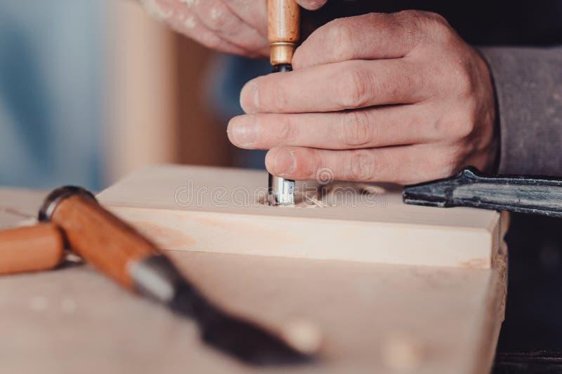 utilisation de charpentier un burin aux formes une planche en bois image libre de droits