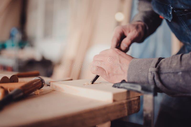 utilisation de charpentier un burin aux formes une planche en bois photo libre de droits
