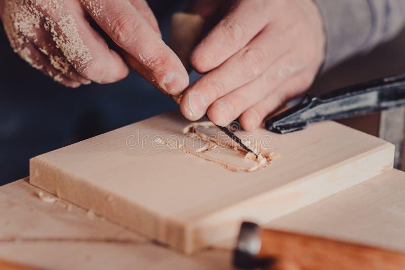 utilisation de charpentier un burin aux formes une planche en bois photos libres de droits