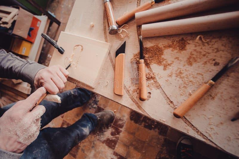 utilisation de charpentier un burin aux formes une planche en bois photos stock