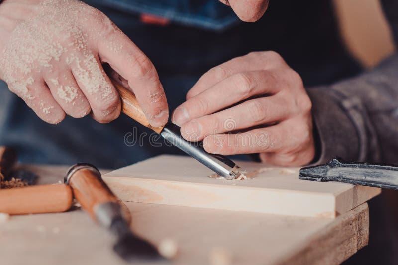 utilisation de charpentier un burin aux formes une planche en bois photographie stock