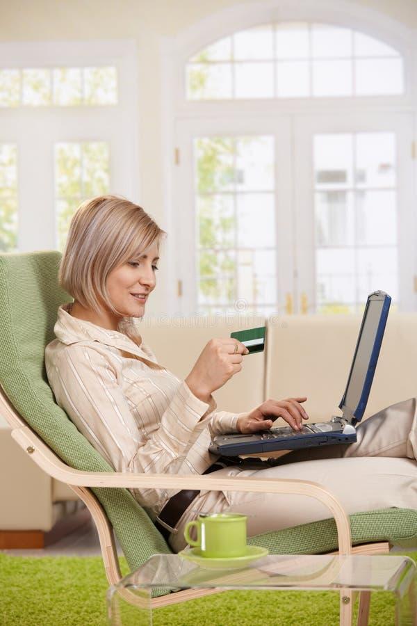 Utilisation de femme par la carte de crédit sur l'Internet. photo libre de droits