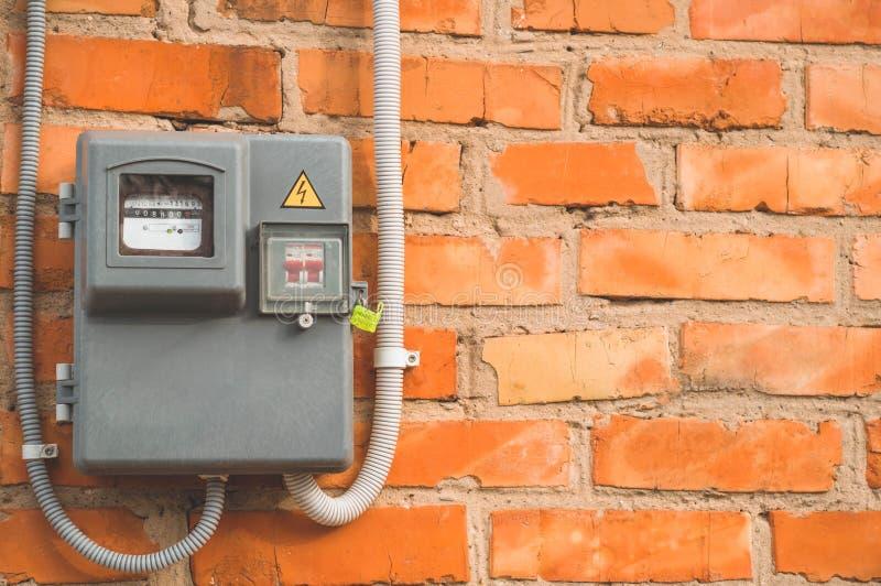 Utilisation de mesure de puissance de m?tre de courant ?lectrique Outil de mesure de m?tre ?lectrique de watt-heure sur le mur de photo stock