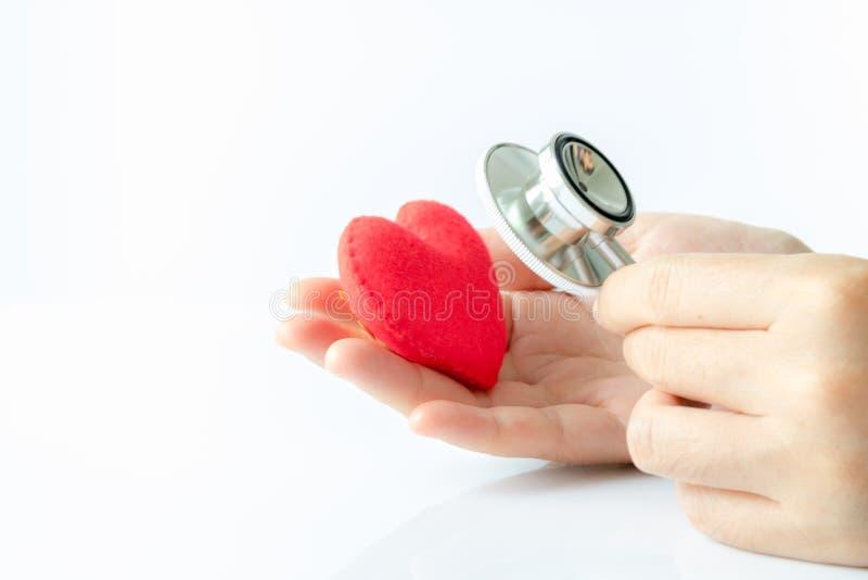 Utilisation de stéthoscope de participation de main d'entendre des bruits dans le coeur rouge photo stock
