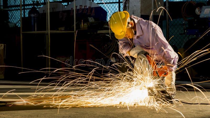 Utilisations de travailleur rectifiant le métal coupé, foyer sur la ligne légère instantanée de l'étincelle pointue, dans la faib photos libres de droits