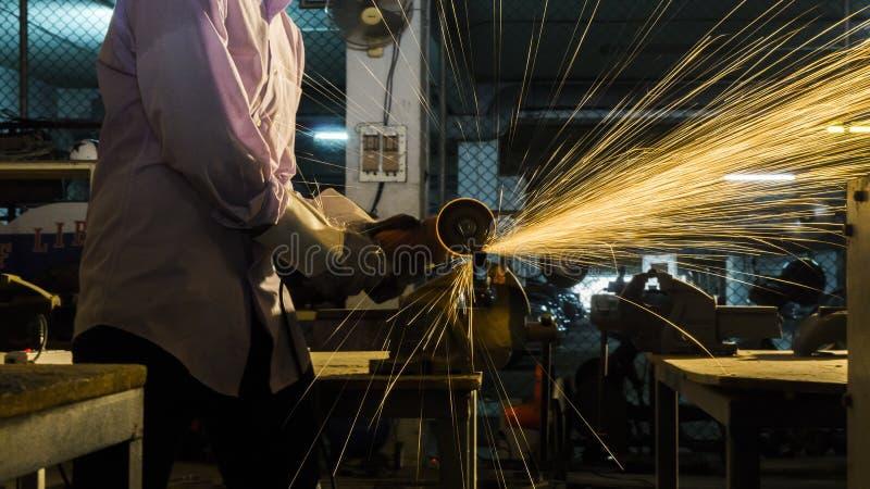 Utilisations de travailleur rectifiant le métal coupé, foyer sur la ligne légère instantanée de l'étincelle pointue, dans la faib photos stock