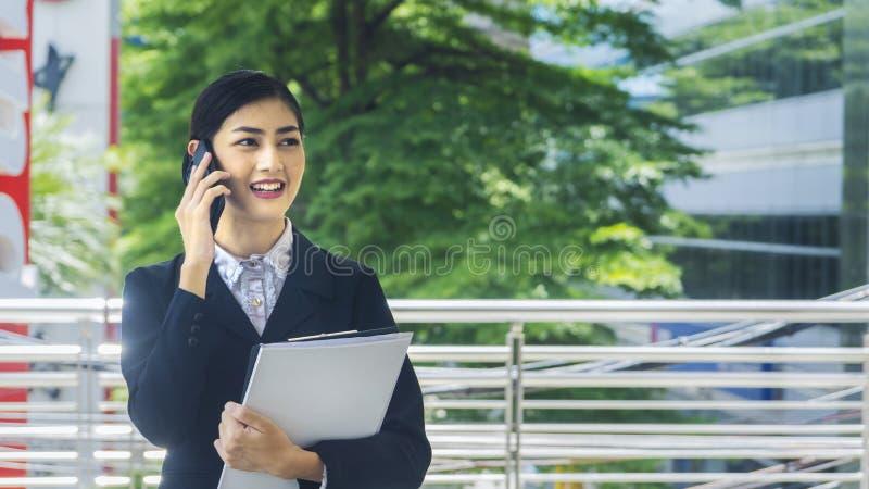 Utilisations et entretiens asiatiques de femme d'affaires au téléphone portable image libre de droits