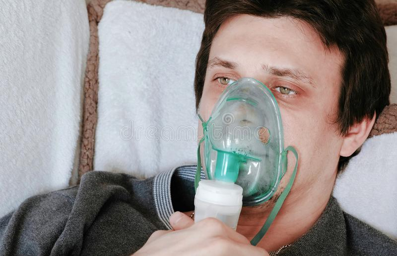 Utilisez le nébuliseur et l'inhalateur pour le traitement Visage du ` s de jeune homme inhalant par le masque d'inhalateur se tro images stock