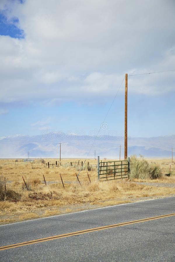 Utility pole in corner of paddock. Cloudy sky. Utility pole in paddock. wood and barbed wire fence with gate in corner. light blue sky with clouds. grassy planes royalty free stock photos